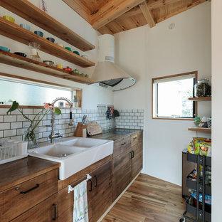 他の地域のコンテンポラリースタイルのおしゃれなキッチン (ダブルシンク、フラットパネル扉のキャビネット、中間色木目調キャビネット、木材カウンター、白いキッチンパネル、サブウェイタイルのキッチンパネル、塗装フローリング、茶色い床) の写真
