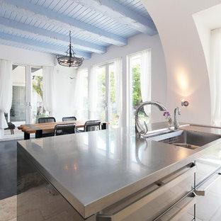 他の地域の地中海スタイルのおしゃれなキッチン (シングルシンク、フラットパネル扉のキャビネット、ステンレスキャビネット、ステンレスカウンター) の写真