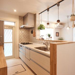 Idées déco pour une cuisine ouverte scandinave avec un évier 1 bac, un placard à porte plane, des portes de placard beiges, une crédence blanche, une crédence en carrelage métro et un sol beige.