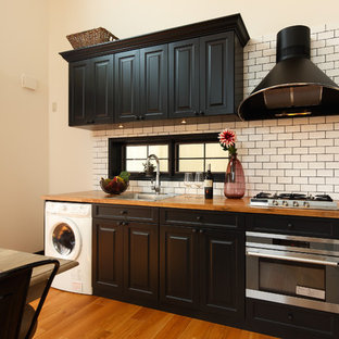 Midcentury single-wall open plan kitchen in Other with a single-bowl sink, raised-panel cabinets, medium wood cabinets, wood benchtops, white splashback, subway tile splashback, black appliances, medium hardwood floors, a peninsula, brown floor and brown benchtop.