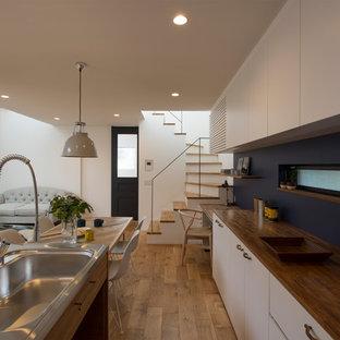 他の地域の北欧スタイルのおしゃれなキッチン (一体型シンク、フラットパネル扉のキャビネット、白いキャビネット、ステンレスカウンター、淡色無垢フローリング、ベージュの床、茶色いキッチンカウンター) の写真