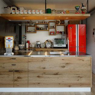 東京23区のカントリー風おしゃれなI型キッチン (シングルシンク、フラットパネル扉のキャビネット、中間色木目調キャビネット、ステンレスカウンター、無垢フローリング、茶色い床) の写真