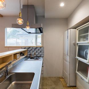 他の地域のアジアンスタイルのおしゃれなキッチン (一体型シンク、フラットパネル扉のキャビネット、ステンレスカウンター、無垢フローリング、茶色い床) の写真