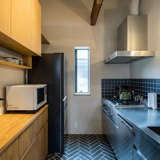 他の地域のコンテンポラリースタイルのおしゃれなキッチン (一体型シンク、フラットパネル扉のキャビネット、ステンレスキャビネット、ステンレスカウンター、黒いキッチンパネル、アイランドなし、黒い床) の写真