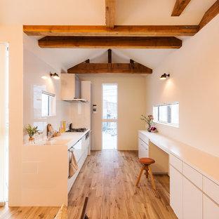 他の地域のアジアンスタイルのおしゃれなキッチン (一体型シンク、フラットパネル扉のキャビネット、白いキャビネット、白いキッチンパネル、無垢フローリング、茶色い床) の写真