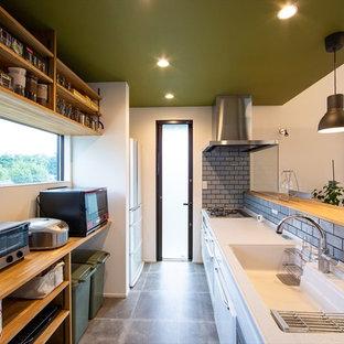 他の地域の中サイズのミッドセンチュリースタイルのおしゃれなキッチン (オープンシェルフ、中間色木目調キャビネット、人工大理石カウンター、グレーのキッチンパネル、セラミックタイルのキッチンパネル、黒い調理設備、白いキッチンカウンター、一体型シンク、グレーの床) の写真