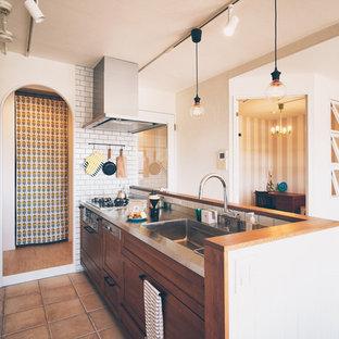 名古屋の北欧スタイルのおしゃれなペニンシュラキッチン (一体型シンク、落し込みパネル扉のキャビネット、ヴィンテージ仕上げキャビネット、ステンレスカウンター、テラコッタタイルの床、茶色い床、茶色いキッチンカウンター) の写真
