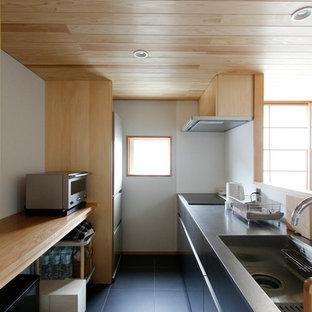 Cette image montre une cuisine linéaire asiatique avec un évier intégré, un placard à porte plane, des portes de placard noires, une crédence blanche, une péninsule, un sol noir et un plan de travail marron.
