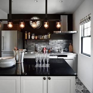 他の地域の北欧スタイルのおしゃれなキッチン (落し込みパネル扉のキャビネット、白いキャビネット、グレーのキッチンパネル、マルチカラーの床) の写真