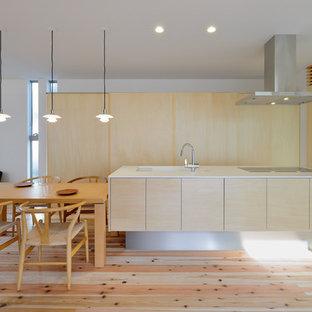 Foto de cocina de galera, de estilo zen, abierta, con fregadero bajoencimera, armarios con paneles lisos, puertas de armario de madera clara, suelo de madera clara, una isla, suelo beige y encimeras blancas