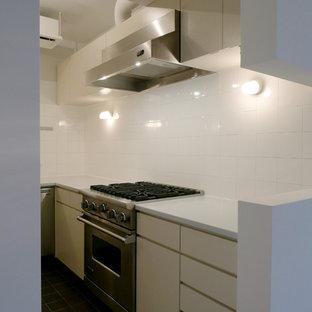 Idee per una cucina a L con ante beige, top in superficie solida, paraspruzzi bianco, paraspruzzi con piastrelle in terracotta, elettrodomestici in acciaio inossidabile, pavimento in terracotta, pavimento nero e top bianco