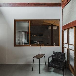 他の地域の巨大な和風のおしゃれなキッチン (一体型シンク、オープンシェルフ、淡色木目調キャビネット、ステンレスカウンター、白いキッチンパネル、磁器タイルのキッチンパネル、黒い調理設備、コンクリートの床、グレーの床、グレーのキッチンカウンター) の写真