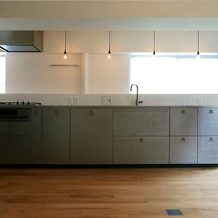 Inspiration for a modern single-wall open plan kitchen in Tokyo with an undermount sink, flat-panel cabinets, stainless steel cabinets, stainless steel benchtops, white splashback, ceramic splashback, stainless steel appliances, light hardwood floors and beige floor.