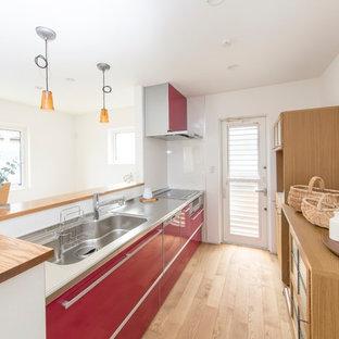 他の地域のコンテンポラリースタイルのおしゃれなキッチン (シングルシンク、フラットパネル扉のキャビネット、赤いキャビネット、ステンレスカウンター、赤いキッチンパネル、淡色無垢フローリング) の写真