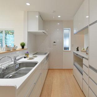 他の地域のモダンスタイルのおしゃれなキッチン (トリプルシンク、人工大理石カウンター、白いキッチンパネル、白い調理設備、淡色無垢フローリング、ベージュの床、白いキッチンカウンター) の写真