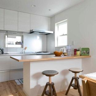 他の地域のモダンスタイルのおしゃれなキッチン (シングルシンク、フラットパネル扉のキャビネット、白いキャビネット、ステンレスカウンター、無垢フローリング、茶色い床) の写真