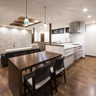 他の地域の中くらいのアジアンスタイルのおしゃれなキッチン (濃色無垢フローリング、茶色い床、一体型シンク、フラットパネル扉のキャビネット、白いキャビネット) の写真