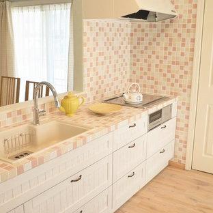 他の地域の地中海スタイルのおしゃれなアイランドキッチン (ドロップインシンク、落し込みパネル扉のキャビネット、白いキャビネット、タイルカウンター、マルチカラーのキッチンパネル、塗装フローリング、茶色い床) の写真