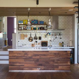 他の地域の大きいインダストリアルスタイルのおしゃれなキッチン (白いキッチンパネル、サブウェイタイルのキッチンパネル、無垢フローリング、オープンシェルフ、黒いキャビネット、御影石カウンター、黒い調理設備、茶色い床、白いキッチンカウンター) の写真