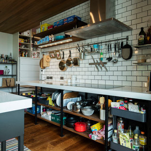 他の地域の広いインダストリアルスタイルのおしゃれなキッチン (一体型シンク、オープンシェルフ、黒いキャビネット、御影石カウンター、白いキッチンパネル、サブウェイタイルのキッチンパネル、黒い調理設備、濃色無垢フローリング、茶色い床、白いキッチンカウンター) の写真