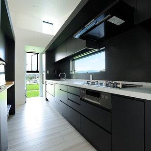 他の地域の広いモダンスタイルのおしゃれなキッチン (黒いキャビネット、人工大理石カウンター、黒いキッチンパネル、シルバーの調理設備、白いキッチンカウンター、シングルシンク、フラットパネル扉のキャビネット、ベージュの床) の写真