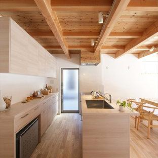 Пример оригинального дизайна: прямая кухня-гостиная в скандинавском стиле с одинарной раковиной, плоскими фасадами, светлыми деревянными фасадами, деревянной столешницей, светлым паркетным полом, полуостровом, бежевым полом и бежевой столешницей