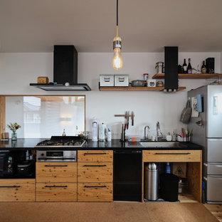 他の地域のコンテンポラリースタイルのおしゃれなキッチン (シングルシンク、フラットパネル扉のキャビネット、中間色木目調キャビネット、白いキッチンパネル、無垢フローリング、茶色い床、黒いキッチンカウンター) の写真