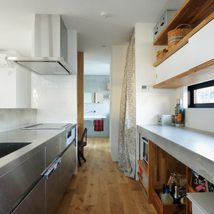 他の地域のアジアンスタイルのおしゃれなII型キッチン (一体型シンク、フラットパネル扉のキャビネット、ステンレスキャビネット、ステンレスカウンター、白いキッチンパネル、ガラスまたは窓のキッチンパネル、シルバーの調理設備の、茶色い床、グレーのキッチンカウンター、淡色無垢フローリング) の写真