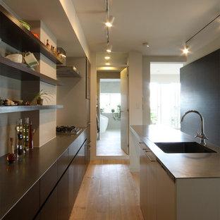 大阪の中くらいのアジアンスタイルのおしゃれなキッチン (一体型シンク、ステンレスカウンター、フラットパネル扉のキャビネット、濃色木目調キャビネット、黒いキッチンパネル、無垢フローリング、茶色い床、茶色いキッチンカウンター) の写真