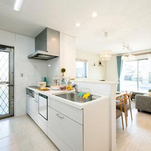 他の地域の北欧スタイルのおしゃれなキッチン (シングルシンク、フラットパネル扉のキャビネット、白いキャビネット、クッションフロア、ベージュの床、白いキッチンカウンター) の写真
