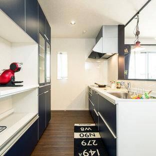 他の地域のコンテンポラリースタイルのおしゃれなキッチン (シングルシンク、フラットパネル扉のキャビネット、ターコイズのキャビネット、濃色無垢フローリング、茶色い床) の写真