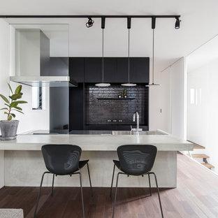 他の地域のモダンスタイルのおしゃれなキッチン (一体型シンク、フラットパネル扉のキャビネット、黒いキャビネット、コンクリートカウンター、黒いキッチンパネル、ガラスタイルのキッチンパネル、パネルと同色の調理設備、無垢フローリング、茶色い床、グレーのキッチンカウンター) の写真