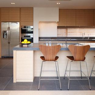 他の地域の広いコンテンポラリースタイルのおしゃれなキッチン (ダブルシンク、フラットパネル扉のキャビネット、中間色木目調キャビネット、ガラスまたは窓のキッチンパネル、磁器タイルの床、グレーの床、グレーのキッチンカウンター) の写真