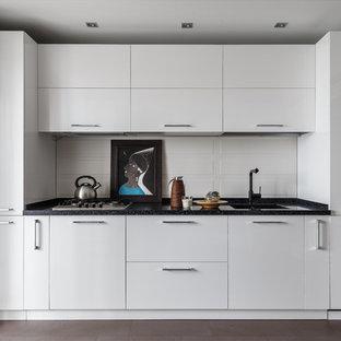 京都のコンテンポラリースタイルのおしゃれなI型キッチン (シングルシンク、フラットパネル扉のキャビネット、白いキャビネット、白いキッチンパネル、アイランドなし、茶色い床、黒いキッチンカウンター) の写真