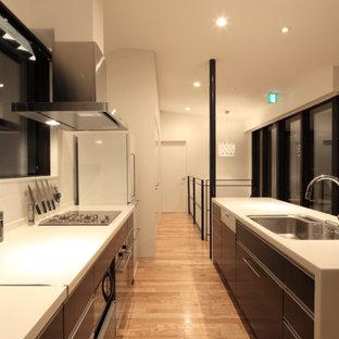 札幌のモダンスタイルのおしゃれなキッチン (シングルシンク、フラットパネル扉のキャビネット、黒いキャビネット、淡色無垢フローリング、茶色い床、白いキッチンカウンター) の写真