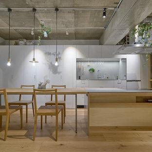 東京23区のモダンスタイルのおしゃれなキッチン (フラットパネル扉のキャビネット、グレーのキャビネット、グレーのキッチンパネル、シルバーの調理設備、淡色無垢フローリング、茶色い床) の写真