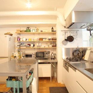 東京23区のアジアンスタイルのおしゃれなキッチン (シングルシンク、フラットパネル扉のキャビネット、白いキャビネット、ステンレスカウンター、メタリックのキッチンパネル、無垢フローリング、茶色い床) の写真