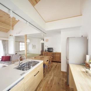 他の地域のカントリー風おしゃれなペニンシュラキッチン (無垢フローリング、茶色い床、シングルシンク、フラットパネル扉のキャビネット、淡色木目調キャビネット) の写真