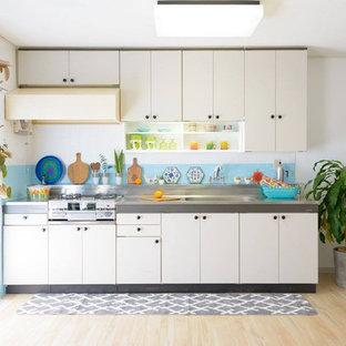 他の地域のコンテンポラリースタイルのおしゃれなキッチン (シングルシンク、フラットパネル扉のキャビネット、白いキャビネット、ステンレスカウンター、青いキッチンパネル、淡色無垢フローリング、茶色い床) の写真