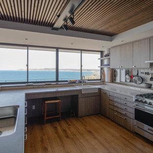 他の地域のビーチスタイルのおしゃれなコの字型キッチン (エプロンフロントシンク、フラットパネル扉のキャビネット、中間色木目調キャビネット、ベージュキッチンパネル、シルバーの調理設備の、無垢フローリング、アイランドなし) の写真