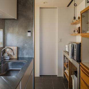 他の地域のアジアンスタイルのおしゃれなII型キッチン (一体型シンク、フラットパネル扉のキャビネット、中間色木目調キャビネット、ステンレスカウンター、白いキッチンパネル、シルバーの調理設備の、グレーの床、グレーのキッチンカウンター) の写真