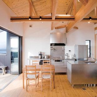 他の地域のコンテンポラリースタイルのおしゃれなキッチン (アンダーカウンターシンク、フラットパネル扉のキャビネット、グレーのキャビネット、ステンレスカウンター、白いキッチンパネル、シルバーの調理設備の、無垢フローリング、茶色い床、グレーのキッチンカウンター) の写真