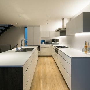横浜のモダンスタイルのおしゃれなキッチン (シングルシンク、フラットパネル扉のキャビネット、白いキャビネット、淡色無垢フローリング、ベージュの床) の写真