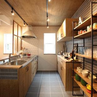他の地域のインダストリアルスタイルのおしゃれなキッチン (一体型シンク、フラットパネル扉のキャビネット、中間色木目調キャビネット、ステンレスカウンター、黒いキッチンパネル、ボーダータイルのキッチンパネル、グレーの床) の写真