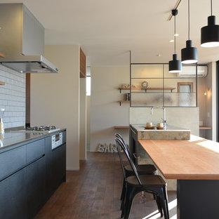 名古屋のインダストリアルスタイルのおしゃれなキッチン (フラットパネル扉のキャビネット、黒いキャビネット、白いキッチンパネル、無垢フローリング、茶色い床) の写真