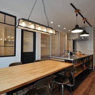 他の地域のインダストリアルスタイルのおしゃれなキッチン (シングルシンク、ステンレスカウンター、塗装フローリング、茶色い床) の写真