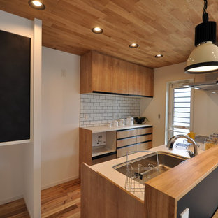 Beach style single-wall kitchen in Other with a single-bowl sink, flat-panel cabinets, medium wood cabinets, medium hardwood floors, a peninsula, pink floor and brown benchtop.
