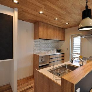 Einzeilige Maritime Küche mit Waschbecken, flächenbündigen Schrankfronten, hellbraunen Holzschränken, braunem Holzboden, Halbinsel, rosa Boden und brauner Arbeitsplatte in Sonstige