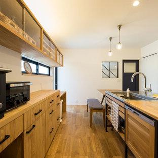 他の地域のモダンスタイルのおしゃれなペニンシュラキッチン (シングルシンク、フラットパネル扉のキャビネット、中間色木目調キャビネット、木材カウンター、無垢フローリング、茶色い床、茶色いキッチンカウンター) の写真