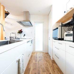 他の地域のモダンスタイルのおしゃれなキッチン (シングルシンク、フラットパネル扉のキャビネット、白いキャビネット、白い調理設備、無垢フローリング、茶色い床、白いキッチンカウンター) の写真